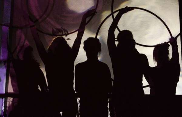 Silhouettes of hula hoopers in circus costumes